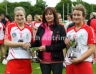 Antrim Camogie Vice Chairman presenting Senior Feis Camogie Final Captain Charlene Campbell with the Senior Feis Camogie Trophy and Emma McMullan with player of the match